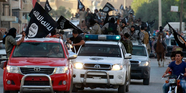"""June 30, 2014: Militant Islamist fighters waving flags, travel in vehicles as they take part in a military parade along the streets of Syria's northern Raqqa province. The fighters held the parade to celebrate their declaration of an Islamic """"caliphate"""" after the group captured territory in nearby Iraq, a monitoring service said."""