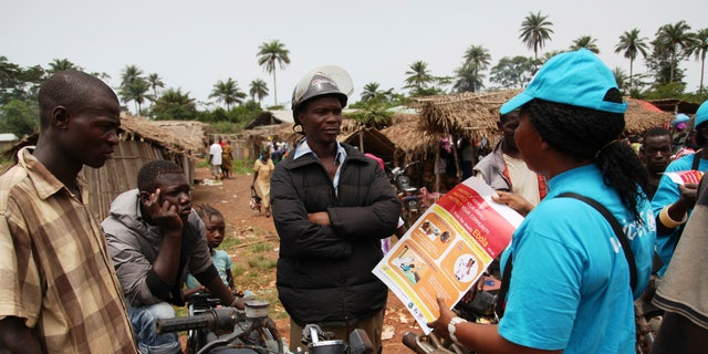 A UNICEF worker speaks with drivers of motorcycle taxis  about the symptoms of Ebola virus disease (EVD) and best practices to help prevent its spread, in the city of Voinjama, in Lofa County, Liberia.  REUTERS