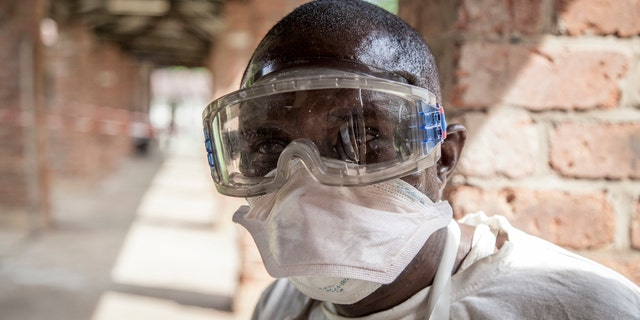 In this photo taken Saturday, May 12, 2018, a health worker wears protective clothing outside an isolation ward to diagnose and treat suspected Ebola patients, at Bikoro Hospital in Bikoro, the rural area where the Ebola outbreak was announced last week, in Congo.
