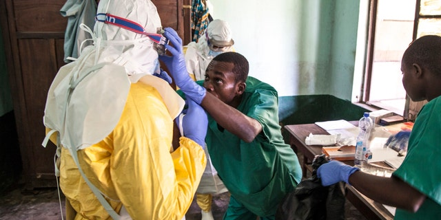 In this photo taken Monday, May 14, 2018, members of a Red Cross team don protective clothing before heading out to look for suspected victims of Ebola, in Mbandaka, Congo.