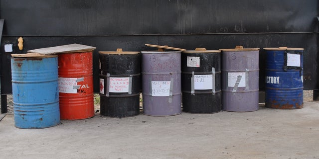Barrels of cremated bodies of Ebola virus victims are seen in Boys Town, January 9, 2015. REUTERS/James Giahyue