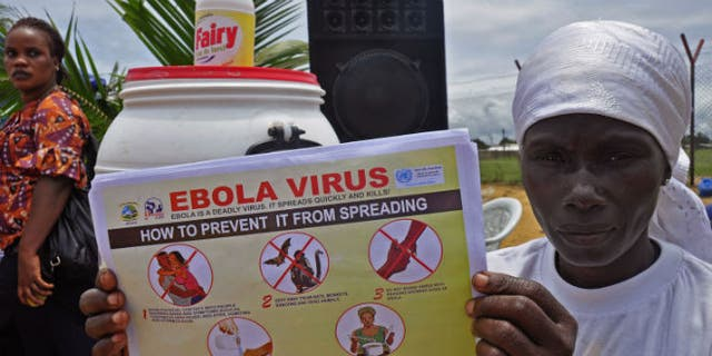 A Liberian woman holds up a pamphlet with guidance on how to prevent the Ebola virus from spreading, in the city of Monrovia, Liberia, Thursday, Aug. 14, 2014. (AP Photo/Abbas Dulleh)