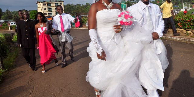 In this photo taken on Saturday, Nov. 15, 2014, an unidentified couple that just got married walk in a park used for wedding photography in the city of  Monrovia, Liberia. (AP Photo/ Abbas Dulleh)
