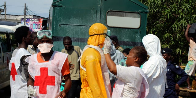 A health worker fixes another health worker's protective suit in the Aberdeen district of Freetown, Sierra Leone, October 14, 2014. REUTERS/Josephus Olu-Mammah