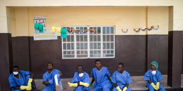 Health workers rest outside a quarantine zone at a Red Cross facility in the town of Koidu, Kono district in Eastern Sierra Leone December 19, 2014. REUTERS/Baz Ratner
