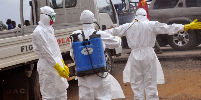 Health workers spray each other with disinfectant chemicals as they worked with a suspected  Ebola virus death in Monrovia, Liberia, Thursday, Sept. 4, 2014. (AP Photo/Abbas Dulleh)