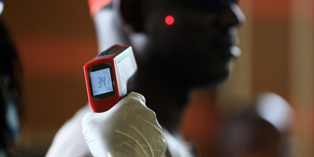 A man has his temperature taken using an infrared digital laser thermometer at the Nnamdi Azikiwe International Airport in Abuja, August 11, 2014. (REUTERS/Afolabi Sotunde)