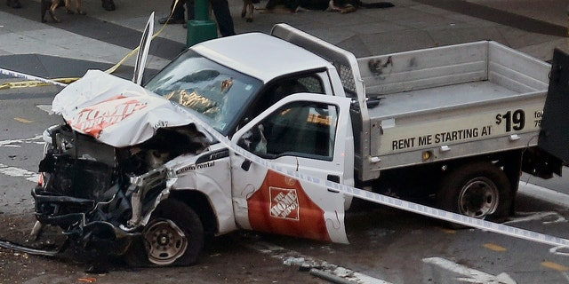 Police tape rests on a damaged Home Depot truck sits after a motorist drove onto a bike path near the World Trade Center memorial, striking and killing several people Tuesday, Oct. 31, 2017, in New York. (AP Photo/Bebeto Matthews)