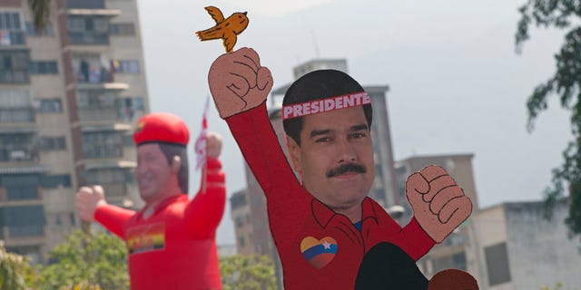 A drawing of ruling party candidate Nicolas Maduro with a bird on his fist with an inflatable doll of the late Hugo Chavez in the background  is held up as supporters move to the site of Maduro's closing campaign rally in Caracas, Venezuela, Thursday, April 11, 2013.  Maduro, Chavez's hand-picked successor,  assured last week during a campaign rally that Venezuela's late President Hugo Chavez's spirit appeared to him in the form of a little bird that flew around his head inside a wooden chapel to give him his blessing. He is running for president against opposition candidate Henrique Capriles in the presidential election set for Sunday, April 14. (AP Photo/Ramon Espinosa)