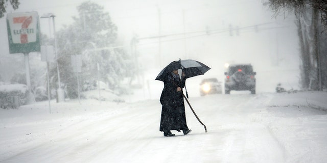 A person tries to cross an icy Pleasure House Rd. in Virginia Beach, Va., during the storm Thursday. Virginia has been socked by a powerful winter blast of snow and cold that's seldom seen along its coast.