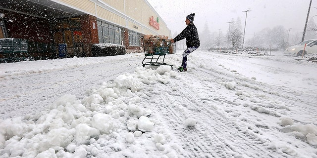 A woman fights to drag her shopping cart to her vehicle after exiting the Shaws Supermarket in Dartmouth, Mass., as a snowstorm swept across the area on Thursday.