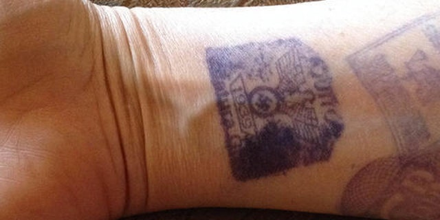 ALTERNATE CROP- In this Sept. 3, 2016, cell phone photo, provided by Maria Isabel Bonilla, shows her arm with prison visitors stamps, one featuring a Nazi Swastika, in Quito, Ecuador. Security guards at the prison were marking visitors with the stamps featuring the emblem of the Nazi Party with an eagle atop a Swastika and the year 1939. Bonilla who's husband is an inmate at the prison posted the photo on twitter causing an immediate uproar, with Ecuadors government immediately condemning the practice. (Maria Isabel Bonilla via AP)