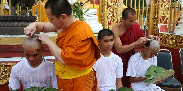 Soccer coach Ekkapol Chantawong, left, and teammates who were rescued last week from a flooded cave have their heads shaved in a traditional Buddhist ceremony in Mae Sai district, Chiang Rai province, northern Thailand.