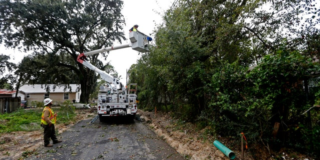 Workers clear trees from power lines in Biloxi, Miss., in the aftermath of Hurricane Nate, Sunday, Oct. 8, 2017.