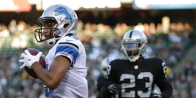 Detroit Lions wide receiver Golden Tate, left, scores on a 28-yard touchdown reception in front of Oakland Raiders cornerback Tarell Brown (23) during the first quarter of an NFL preseason football game in Oakland, Calif., Friday, Aug. 15, 2014. (AP Photo/Marcio Jose Sanchez)