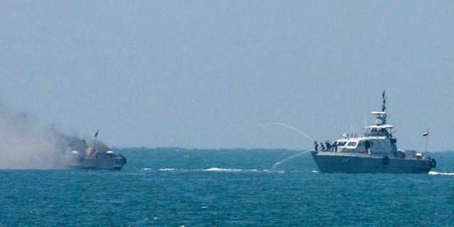 Egyptian navy vessel hoses down another which caught on fire at Mediterranean Sea Thursday, July 16, 2015. An Egyptian navy vessel caught fire off the coast of Sinai on Thursday after an exchange of gunshots with militants from the shore, the military said. (AP Photo/Eyad Baba)