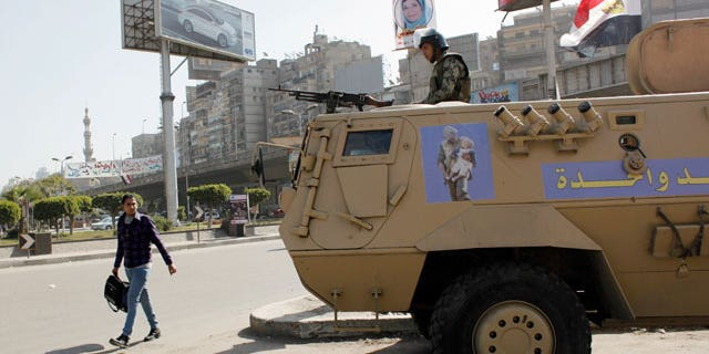 """Feb. 11, 2012: An Egyptian man passes by an army patrol with a soldier on top of an armored vehicle flying the national flag and a sticker on the body with Arabic that reads """"the army and the people are one hand,"""" during a general strike in Cairo, Egypt."""