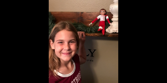 "Aubrie poses with her repaired Elf on the Shelf, ""Sam."""