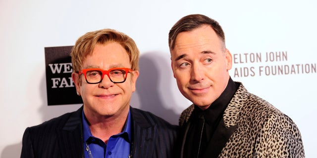 Elton John (L) and David Furnish arrive at the 2014 Elton John AIDS Foundation Oscar Party in West Hollywood, California.