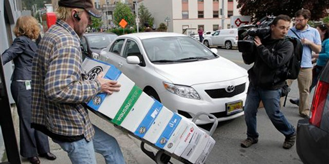 A worker rolls a cart with boxes containing thousands of pages of Sarah Palin's emails from her time as Alaska's governor June 10 in Juneau, Alaska.