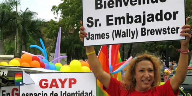 "FILE - In this June 30, 2013 file photo, people welcome U.S. Ambassador James ""Wally"" Brewster during a gay pride parade in Santo Domingo, Dominican Republic. The signs read in Spanish ""Welcome Mr. Ambassador James ""Wally"" Brewster,"" right, and ""Identity space, equality zone."" Activists say Brewster's presence has helped a cultural shift that has allowed gay Dominicans to run for office openly as homosexuals. âWally has become an iconic figure in the LGBT movement because the movement does have strong local figures,â said prominent activist Alexander Mundary. (AP Photo/Ezequiel Abiu Lopez, File)"