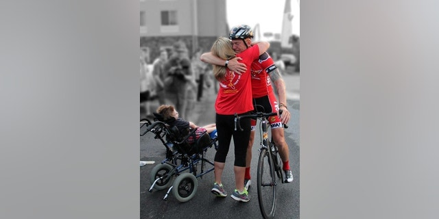 Cyclist Dave Nazaroff meets the Halstead family during a charity race in 2013 to benefit Tripp.