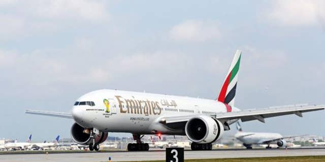 An Emirates aircraft taxis down the runway.