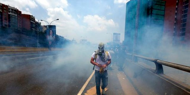 A demonstrator walks in the middle of a cloud of tear gas fired by the Bolivarian National Guard during a protest in Caracas, Venezuela, Monday, April 10, 2017.