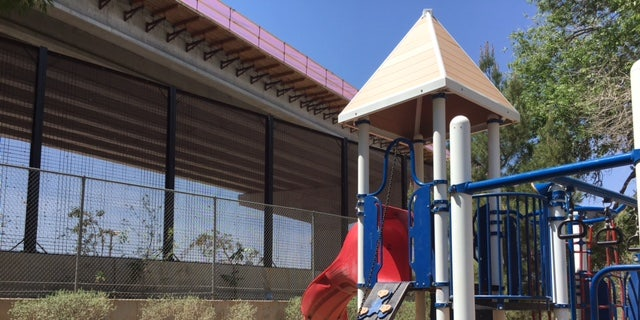 The border fence sits above a children's playground in downtown El Paso.