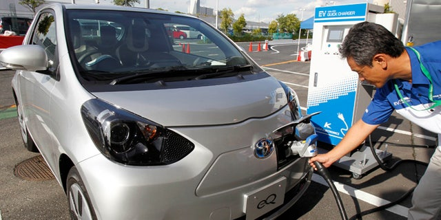 """A participant to a press event by Toyota Motor Corp. puts a quick charger plug into the newly-developed compact electric vehicle """"eQ"""" during a test drive at a press event in Tokyo Monday, Sept. 24, 2012. Toyota is boosting its green vehicle lineup, with plans for 21 new hybrids in the next three years, a new electric car later this year and a fuel cell vehicle by 2015 in response to growing demand for fuel efficient and environmentally friendly driving. (AP Photo/Koji Sasahara)"""