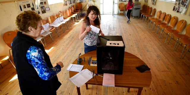 Presiding officer Carmel McBride looks on as a woman casts her vote in the referendum on the 8th Amendment of the Irish Constitution