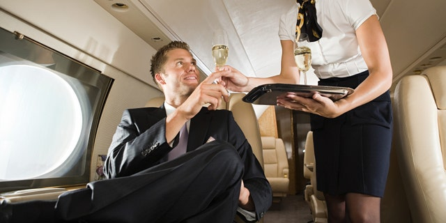 Stewardess handing champagne to man