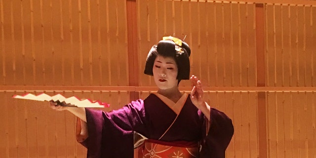 A geisha performs a traditional dance.