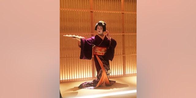 A geisha performs a traditional dance.