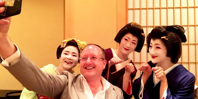 Alex Porteous, General Manager of the Four Seasons Kyoto, takes a selfie with the working geishas.