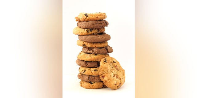 Stack of several chocolate and hazelnut cookies with chocolate chips and cranberies