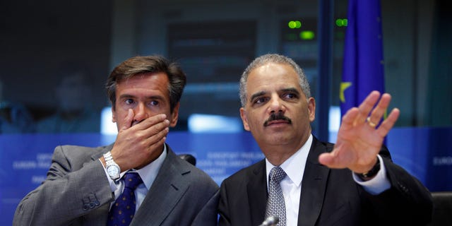 Spanish MEP Juan Fernandez Aguilar, left, looks on as United States Attorney General Eric Holder, right, speaks during a session at the European Parliament in Brussels on Tuesday, Sept. 20, 2011.