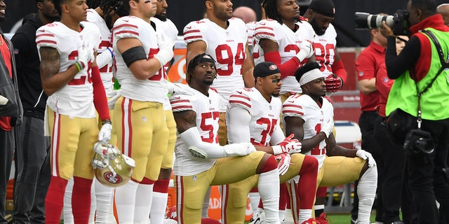 Eric Reid (35) kneels during the national anthem with San Francisco 49ers teammates.