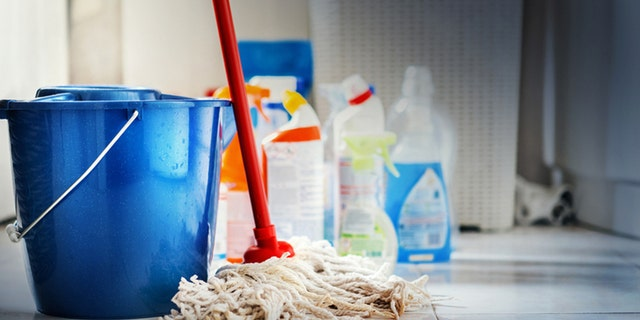 Closeup of unrdcognizable home cleaning products with blue bucket and a mop in front in sharp focus. All products placed on white and poorly lit bathroom floor.