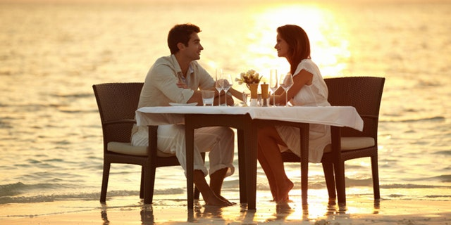 A young couple share a romantic dinner on the beach in the Maldives