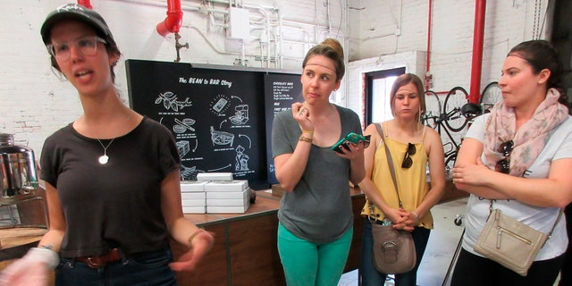 This April 28, 2017 photo shows a group from A Slice of Brooklyn chocolate tour on a visit to Raaka Chocolate in the Red Hook section of Brooklyn, N.Y. Facilities manager Sophie Berman is shown discussing the chocolate-making process, wearing a green cap. Raaka is one of several stops on the tour, which offers chocolate samples to taste along with visits to interesting neighborhoods and insight into how some of the businesses on the tour got started. (AP Photo/Beth J. Harpaz)