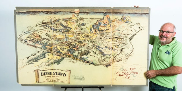 In this April 28, 2017, photo art dealer Mike Van Eaton stands next to a hand-drawn map from 1953 that shows Walt Disney's original ideas for Disneyland displayed at the Van Eaton Galleries in Sherman Oaks area of Los Angeles. Van Eaton Galleries announced that the map is the highlight among dozens of Disney items being auctioned on June 25. (AP Photo/Damian Dovarganes)