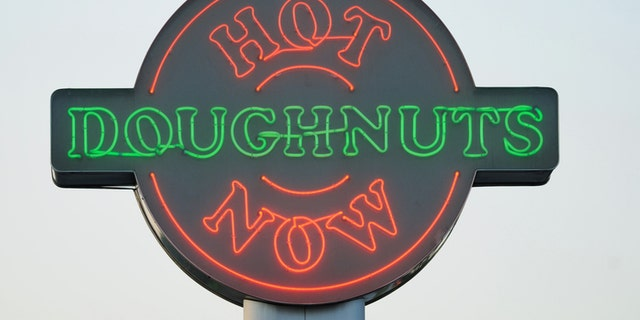 Huntsville, Alabama, USA - July 17, 2011:  Close up of illuminated neon Hot Doughnuts Now sign at Krispy Kreme store.  Sign located on North Memorial Parkway near Cook Avenue in Huntsville, Alabama.