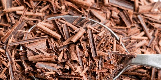 Dark chocolate shavings in metal spoon.