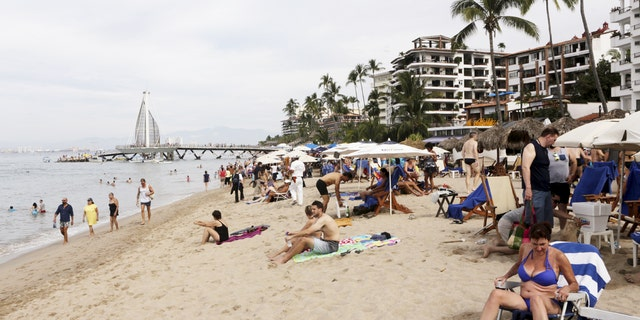 Tourists are seen along the beach resort of Puerto Vallarta, Mexico, December 31, 2015. REUTERS/Henry Romero - RTX20OU9