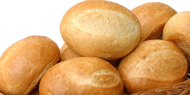 fresh baked rolls in a basket on white