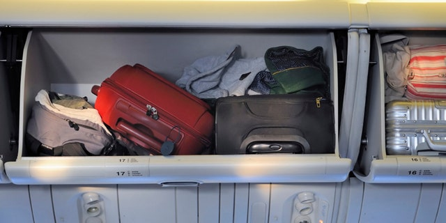 Carry-on luggage in overhead storage compartment on commercial airplane.
