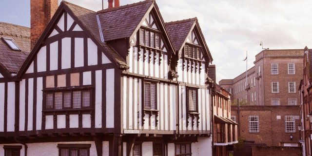 Half-Timbered English building by a small cobblestoned small street.