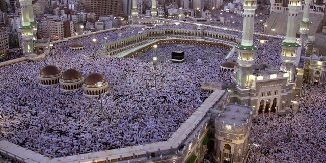 FILE- In this Monday, Feb. 18, 2002 file photo, thousands of Muslims gather around the holy Kabaa during evening prayer in the holy city of Mecca in Saudi Arabia. As Muslims from around the world stream into Mecca for the annual hajj pilgrimage this week, they come to a city undergoing the biggest transformation in its history. (AP Photo/Hasan Sarbakhshian, File)