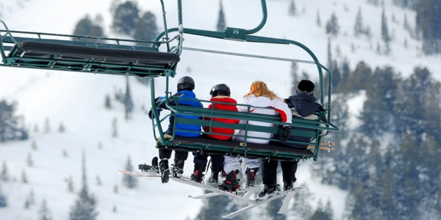 Family of four riding the chairlift at ski resort!